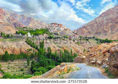 Beautiful scenic view: ancient Likir Buddhist Monastery (Klu-kkhyil Gompa) and twisty mountain road against the background of dramatic sky; Leh, Ladakh range, Himalaya, Jammu & Kashmir, Northern India - stock photo