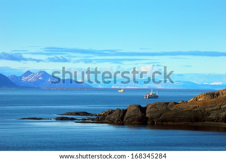 Beautiful scenic view of blue gulf with two floating boats against the background of barren mountain range and dramatic blue sky near Barentsburg, Spitsbergen (Svalbard island), Norway, Greenland sea  - stock photo