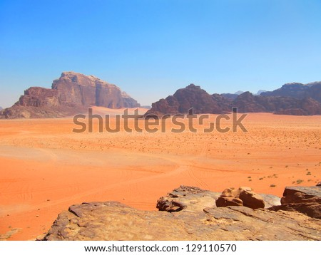 Beautiful scenic view of colorful desert sands and rocks against the background of distant violet rugged mountain range and clear blue sky in Wadi Rum, Jordan, Middle (Near) East, Western Asia - stock photo
