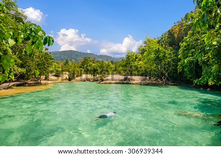 beautiful scenic view of emerald lake , green forest , blue sky with traveler swimming in lake