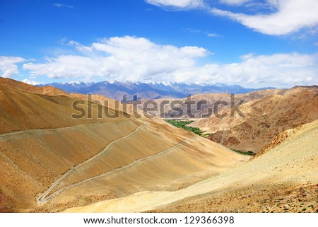 Beautiful scenic view of high mountain serpentine road in smooth hillside of Ladakh range against the background of dramatic blue sky, Leh district,  Jammu & Kashmir, Northern India, Central Asia - stock photo