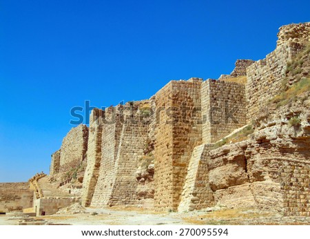 Beautiful scenic view of massive wall in ancient crusader fortress - The Al Karak (UNESCO World Heritage Site)- against the background of bright blue sky in Jordan, Middle East - stock photo