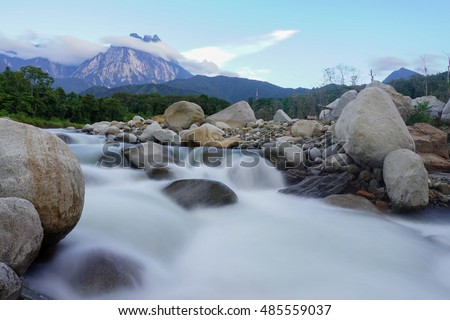 Beautiful scenic view of mountain river flowing across tropical hills and boulders with Mount Kinabalu at the background during sunset in Kota Belud Sabah Malaysian Borneo.
