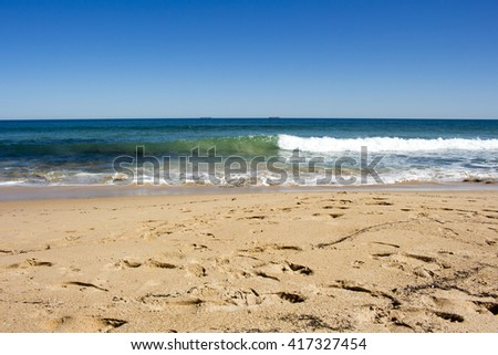 Beautiful scenic view of the sandy beach with footprints   near the Indian Ocean at  isolated Buffalo Beach near Bunbury Western Australia on a calm  tranquil spring  morning. - stock photo