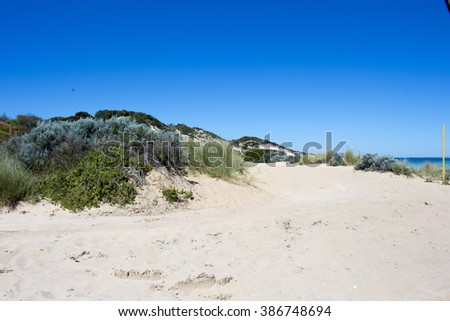 Beautiful scenic view of the sandy dunes  near the Indian Ocean at  isolated Buffalo Beach near Bunbury Western Australia on a calm  tranquil spring  morning. - stock photo