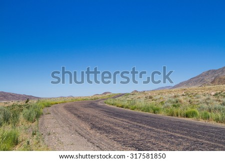 Beautiful scenic view - twisty road across the dry arid land between barren mountains against the background of vivid blue sky, Tien Shan range, Kyrgyzstan, Central Asia