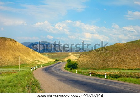 Beautiful scenic view - twisty road across the green field between barren yellow and violet mountains against the background of dramatic cloudy sky, Tien Shan range, Kyrgyzstan, Central Asia - stock photo