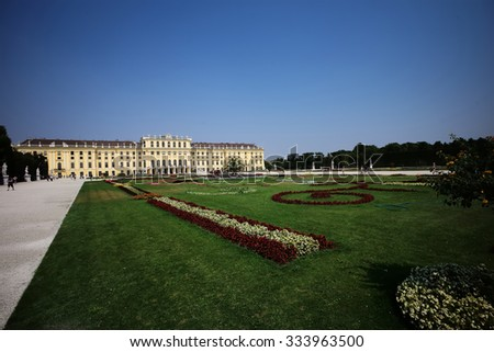 Beautiful schonbrunn medieval baroque palace imperial residence of habsburg dynasty old historical showplace yellow-colored building with green grass garden outdoor on blue sky background, horizontal  - stock photo