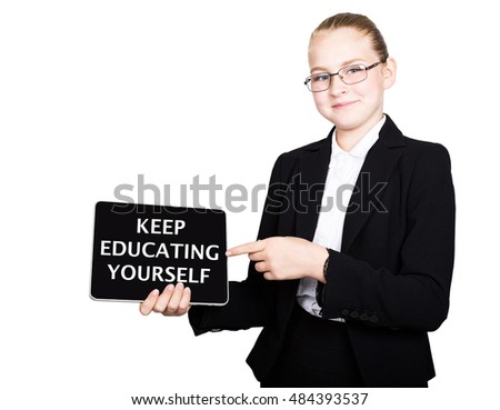 Beautiful school girl in a business suit holds a pc tablet in his hands and looking into the camera, on a pc tablet inscription keep education yourself
