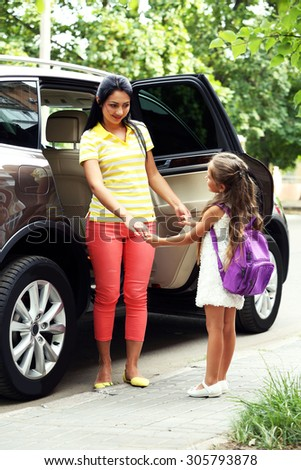 Beautiful school girl with mother near car - stock photo