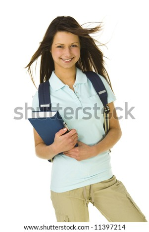 Beautiful schoolgirl holding book. Looking at camera and smiling. Front view. White background.