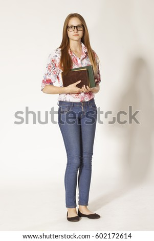 Beautiful schoolgirl with glasses, books and beauty smile