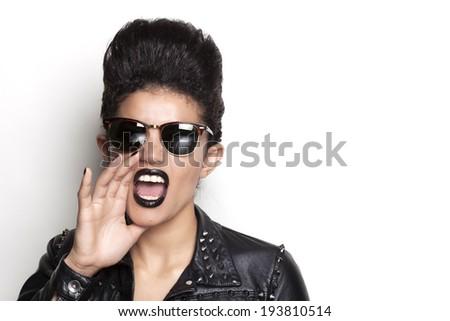 Beautiful screaming woman wearing sunglasses and leather jacket - stock photo