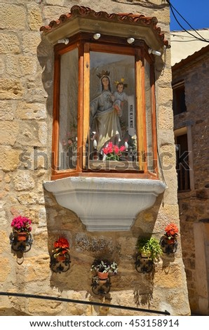 Beautiful sculpture of St. Maria on a wall of an old house in Spanish town - stock photo