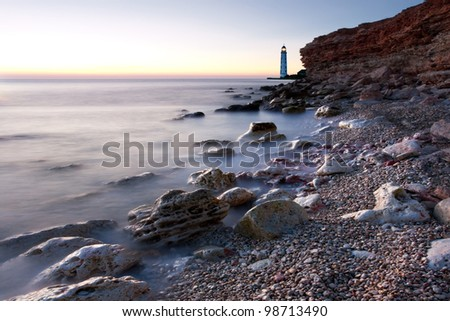 Beautiful sea beach with lighthouse and clear sky at the sunset