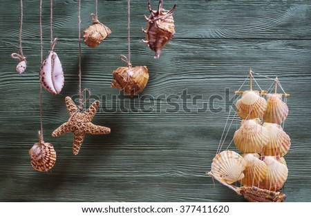 Beautiful sea composition with ship, seashells, starfish, copy space on wooden background.Marine still life with toy model of ship made of cockleshells.Travel and adventure concept - stock photo