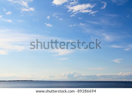 Beautiful sea under cloudy blue sky - stock photo