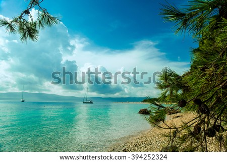 Beautiful sea view on island Brac in Croatia with yacht and rocky beach - stock photo