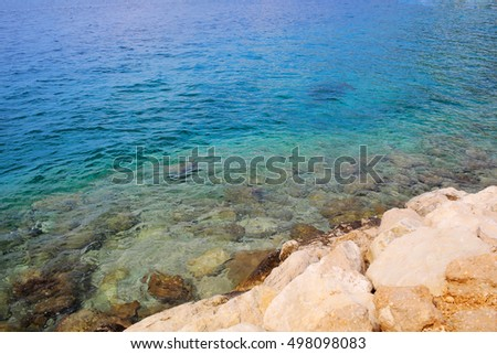 Beautiful sea with clear blue water and rocky shore beach on sunny summer seascape