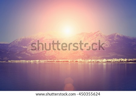 Beautiful seascape: calm water, resort town, high mountains and cloudy sky in the sunlight. Toned