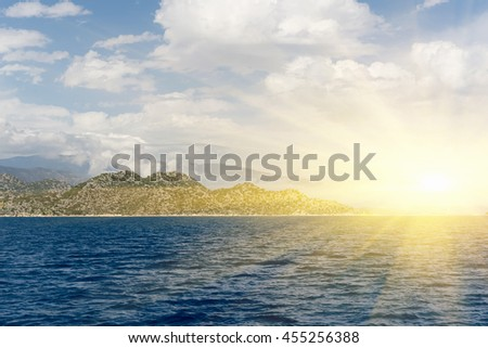 Beautiful seascape: calm water, rocks and cloudy sky in the sunlight - stock photo