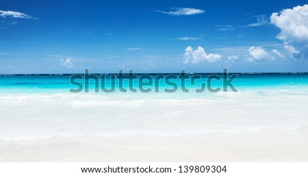 Beautiful seascape, clean turquoise sea, white sandy coastland, blue sky, exotic beach, luxury resort, summer vacation and holiday concept - stock photo