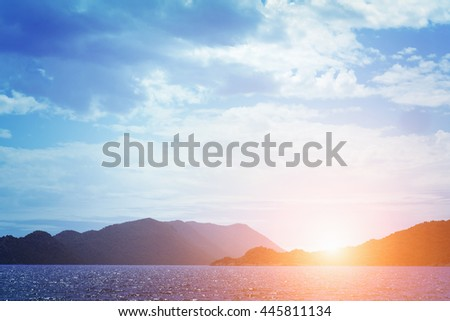 Beautiful seascape: green mountains, calm water and cloudy sky at sunrise or sunset. Toned - stock photo