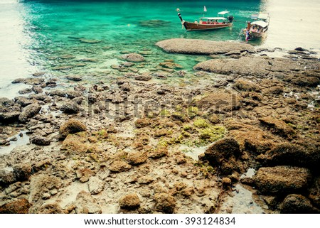 Beautiful seascape. Long-tail boats with tourists in Maya Bay, Phi-Phi islands, Krabi, Thailand. Image with selective focus and toning - stock photo