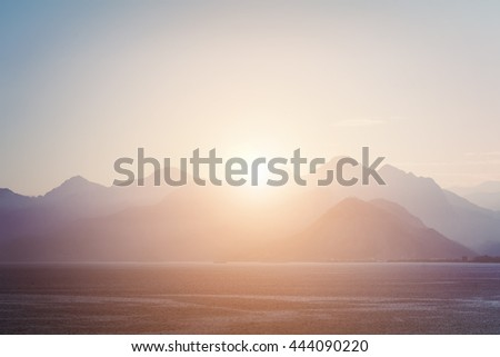 Beautiful seascape: mountains and calm water at sunrise or sunset. Toned - stock photo