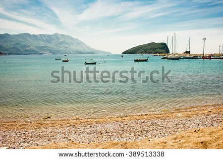 Beautiful seascape overlooking the Adriatic bay and the island of St. Peter in Budva, Montenegro. Sea view, bright blue sky and sandy beach on a sunny day. - stock photo