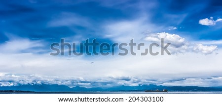 Beautiful seascape panorama view of Aegean sea and Olympus mountains with tanker ship on the background under breathtaking cloudy blue sky.Thessaloniki,Greece - stock photo
