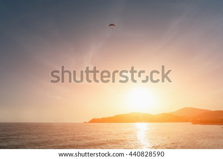 Beautiful seascape: paraglider in the sky over water and mountains at sunrise or sunset - stock photo