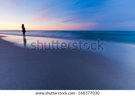 Beautiful seascape sunset with person - stock photo