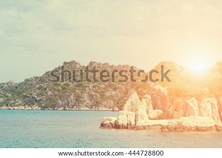 Beautiful seascape: water and rocks in the sunlight. Toned - stock photo