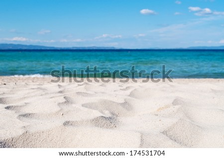 Beautiful seascape with focus on the sand and blurred sea and sky in the background - stock photo