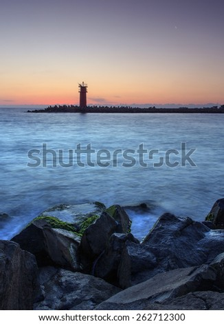 Beautiful seascape with lighthouse at the sunrise - stock photo