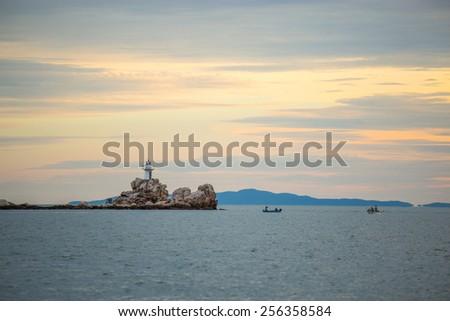 Beautiful seascape with lighthouse on sunrise. - stock photo