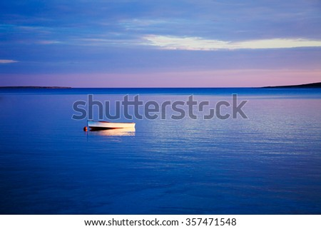 Beautiful Seascape with Lonely White Boat Floating in Blue Sea at Sunset. Peaceful Background with Tranquil Calm Water and Reflection. Copy Space. - stock photo