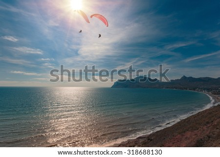 Beautiful seascape with of seashore and couple of paragliders flying over - stock photo
