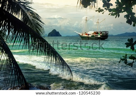 Beautiful seascape with sailing on the sea of old ships against cloudy sky and islands