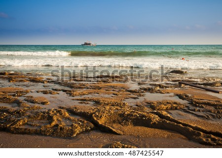 Beautiful seascape with silhouette of walkers on a sandy beach in summertime