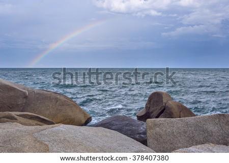 Beautiful seascape with waves splashing against a rocky shore  and rainbow over overcast sky. Samui Island, Thailand - stock photo