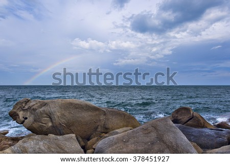 Beautiful seascape with waves splashing against a rocky shore  and rainbow over overcast sky. Samui Island, Thailand
