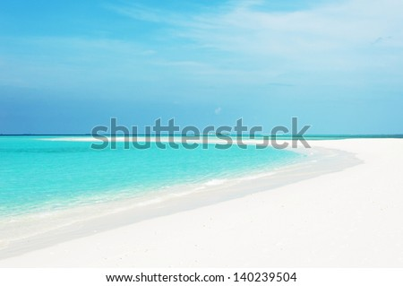 Beautiful seascape with white sand on the beach and blue water on the sea - stock photo