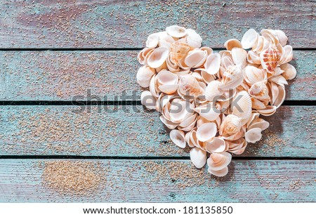 Beautiful seashell heart formed of multiple small bivalves, cones and conches on rustic weathered wooden boards with copyspace for a nautical Valentines or anniversary greeting - stock photo