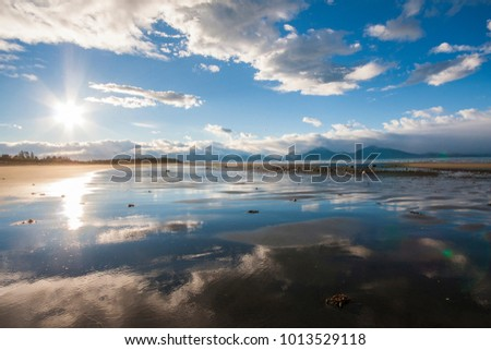 Beautiful seashore at low tide in a sunny day; boreal region of Alaska with blue sky. Midday sky is reflected on water; perfect reflection.