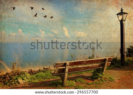 Beautiful seaside with old wooden bench, lantern and migrating birds flying in the sky.  Image done in retro style the on textured old paper background  - stock photo