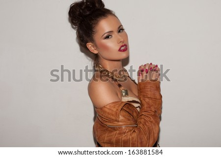 Beautiful seductive elegant woman in a leather jacket and jewellery with her hair in a bun posing on a grey studio background - stock photo