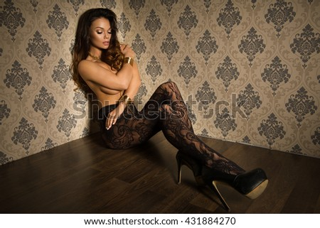 Beautiful, seductive woman sitting in sexy pose wearing alluring tights and heels in style room  - stock photo
