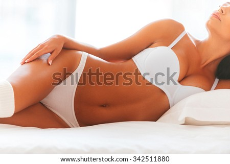 Beautiful seductress. Cropped image of beautiful young woman in lingerie and white socks lying in bed - stock photo